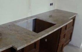 Светло-коричневый мрамор, отверстие под квадратную кухонную мойку и интересная форма столешницы